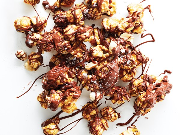 Chocolate-drizzled caramel corn on parchment paper