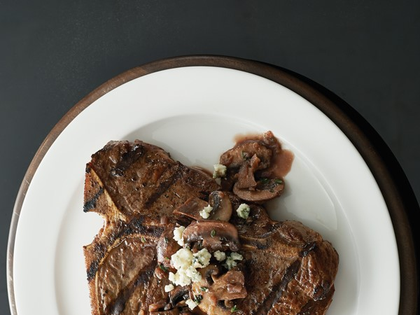Grilled t-bone steaks topped with sauteed mushrooms and crumbled blue cheese