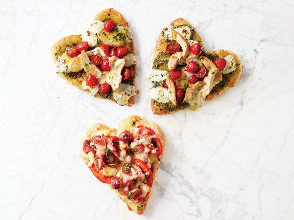 Three heart shaped pizzas with various toppings