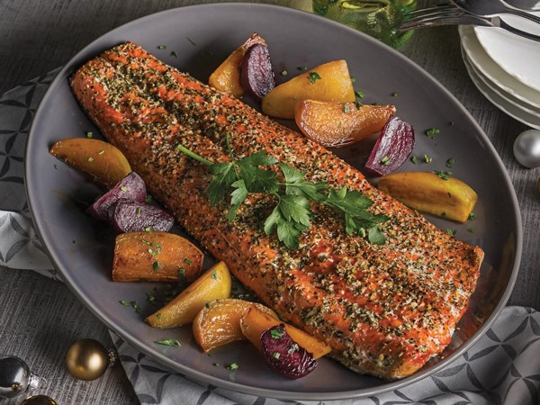 Pesto rubbed salmon on a large platter with roasted vegetables and garnished with parsley