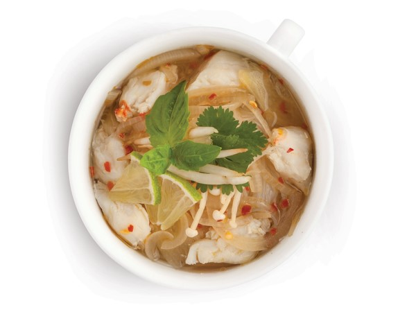Bowl of Alaska crab pho topped with fresh cilantro and lime wedges