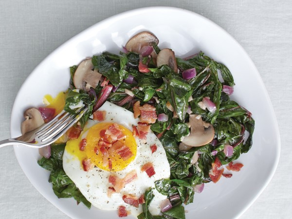 Plate of sauteed chard and eggs, garnished with red onion, mushrooms and bacon crumbles