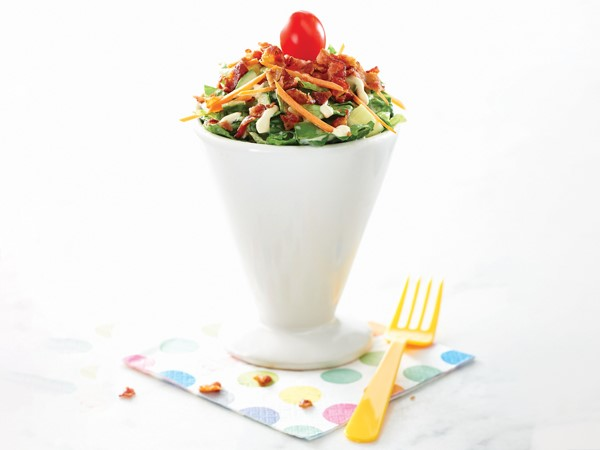 Glass of lettuce sprinkled with bacon, shredded carrot and a cherry tomato