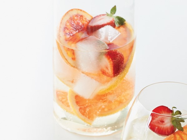Glass of citrus-berry sangria filled with sliced grapefruit and strawberries