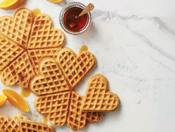 Heart-shaped almond-orange waffles topped with syrup