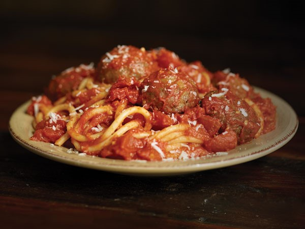 Plate of bucatini pasta topped with tomato pasta sauce and meatballs