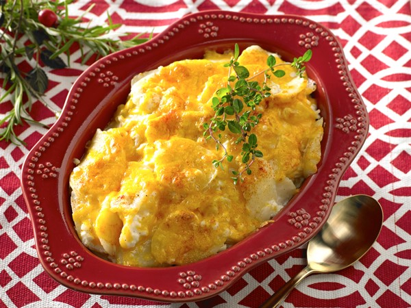 Red dish filled with potato casserole and topped with cheddar cheese and paprika
