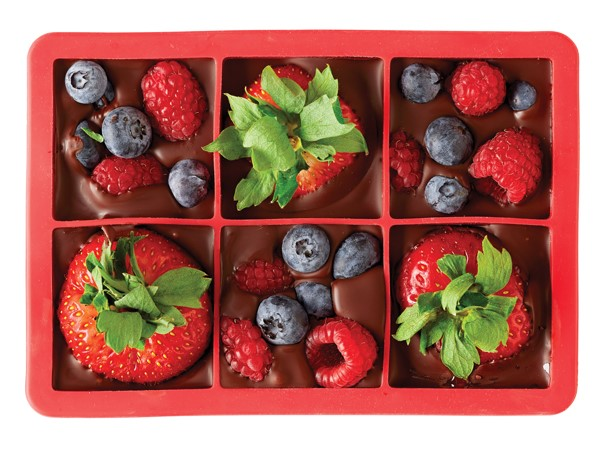Red ice cube tray filled with melted chocolate and strawberries, blueberries and raspberries