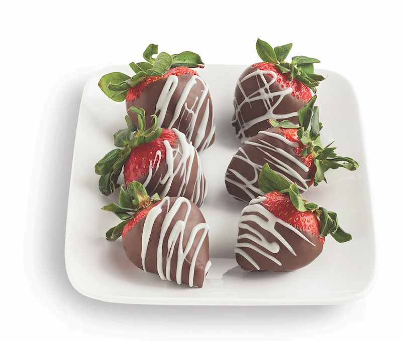 White platter of strawberries covered in milk chocolate and drizzled in white chocolate