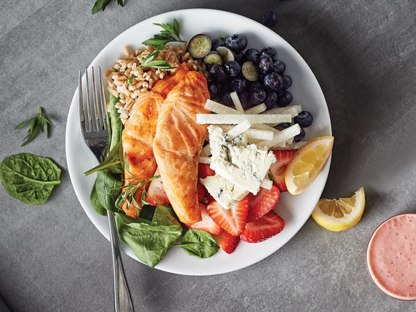 White plate filled with spinach, sliced strawberries, blueberries, farro, sliced jicama, two pieces of salmon, and sliced Gorgonzola cheese