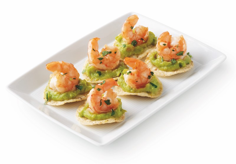 Platter of tortilla chips topped with guacamole and shrimp