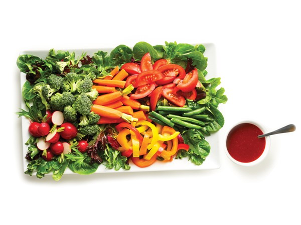 Platter of greens topped with radishes, broccoli, carrots, peppers, tomatoes and peas and served with a side of raspberry vinaigrette