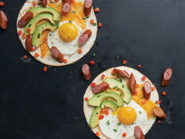 Tortilla topped with cheese, egg, avocado, sausage, onion and tomato
