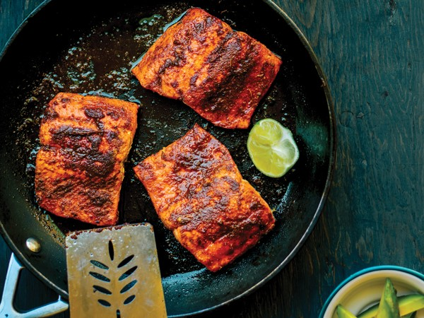 Three salmon fillets in skillet with wedge of lime
