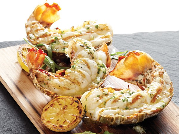 Planked lobster tails with grilled lemons on wooden slab