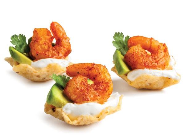 Scoop tortilla shells filled with sour cream, avocado slice, cilantro and seasoned shrimp
