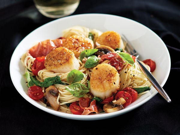 Bowl of angel hair pasta topped with seared scallops, chopped prosciutto, grape tomatoes, mushrooms, garlic and spinach and garnished with fresh basil leaves