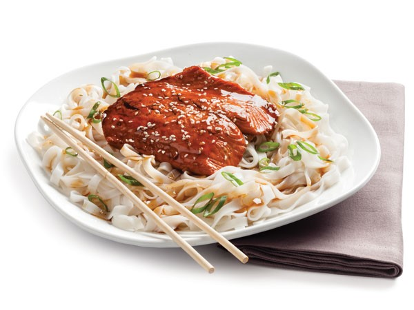 Plate of Asian-glazed salmon fillets over cooked rice noodles and green onion with wooden chopsticks
