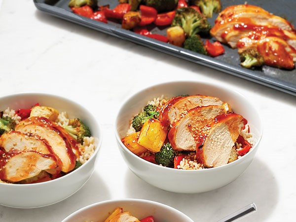 Bowls of sweet and sour chicken served with rice and vegetables