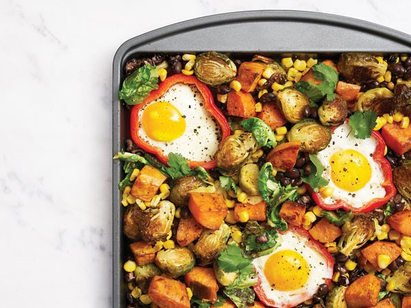 Tray of baked brussels sprouts, potatoes, corn and beans, with eggs baked in bell pepper rings