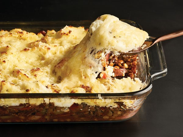 Casserole dish filled with shepherds pie with a serving spoon