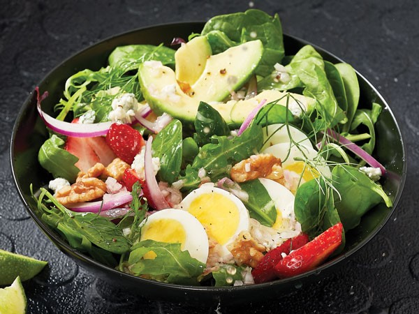 Bowl of greens mixed with strawberries, avocado, hard-boiled eggs, onion and pecans