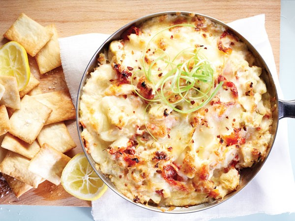 Bowl of artichoke king crab dip garnished with green onions and surrounded by crackers on a wooden board