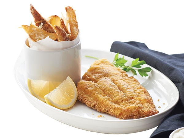 White plate filled with cornmeal-crusted catfish and side of parmesan potato wedges