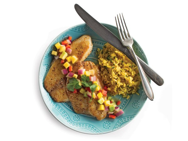Blue plate filled with tilapia covered in fruit salsa, served with a side of rice