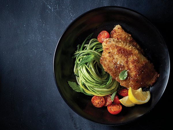 Breaded and seasoned tilapia next to fresh zucchini pasta, blistered and halved cherry tomatoes with fresh slices of lemon and mint leaves for garnish
