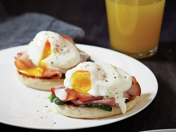 English muffins topped with ham, poached eggs, and sauce served on a plate