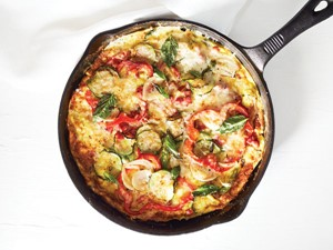 Cast iron baked ham frittata with fresh veggies and garnished with basil