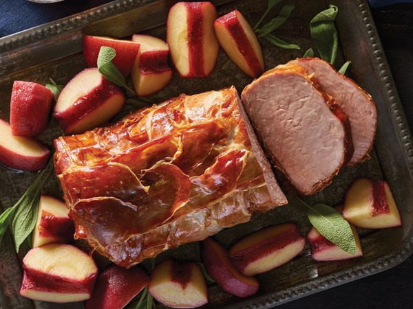 Pork loin wrapped in prosciutto garnished with sage and fresh fruit
