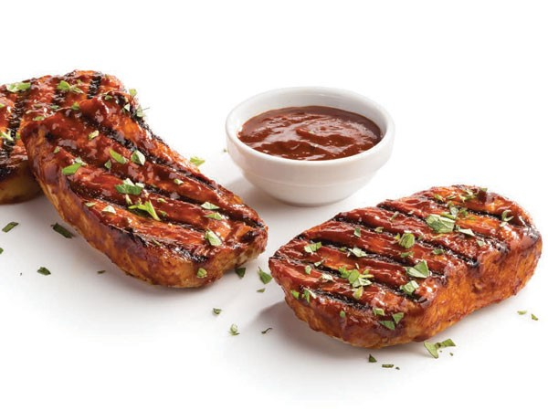 Grilled hot spicy pork chops with sauce and garnished with fresh parsley