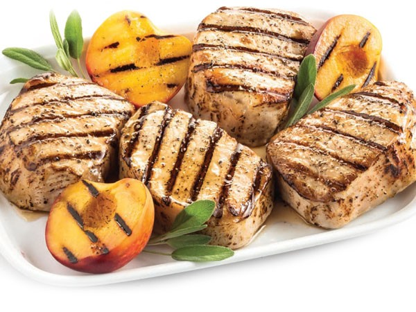 Grilled honey glazed pork chops garnished with sage and grilled peaches