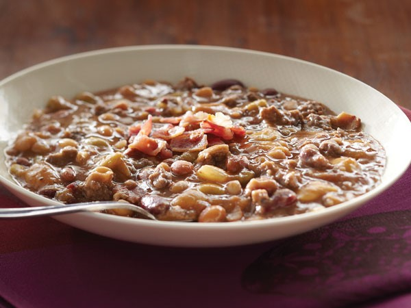 Bowl of calico beans topped with bacon crumbles