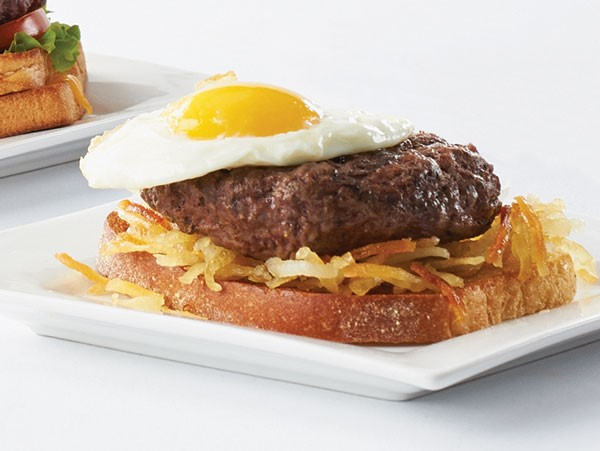 Gourmet burger served atop a bed of hashbrowns and toast and topped with a sunny side up egg