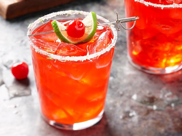 Sugar-rimmed glass filled with cherry-lime margarita, garnished with lime slice and maraschino cherry