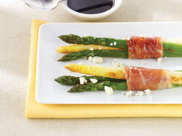 White and green asparagus wrapped with prosciutto and garnished with crumbled cheese
