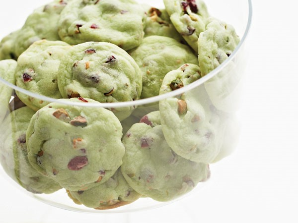Green pistachio cherry cookies in clear glass bowl