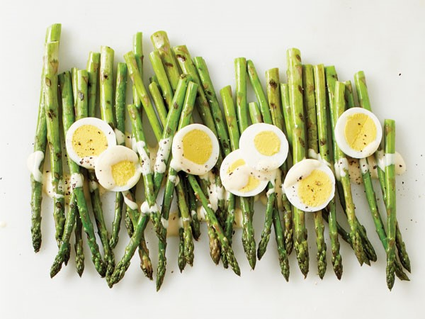 Pile of grilled asparagus topped with cheese sauce, egg slices and freshly ground pepper