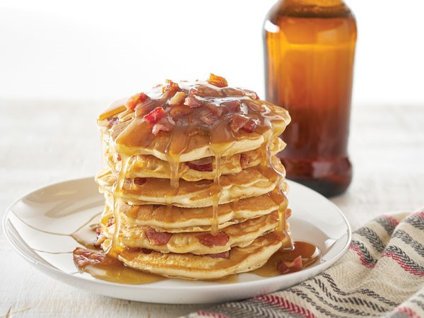 White plate with stacked pancakes dripping with syrup and topped with cooked, chopped bacon and beer bottle in background