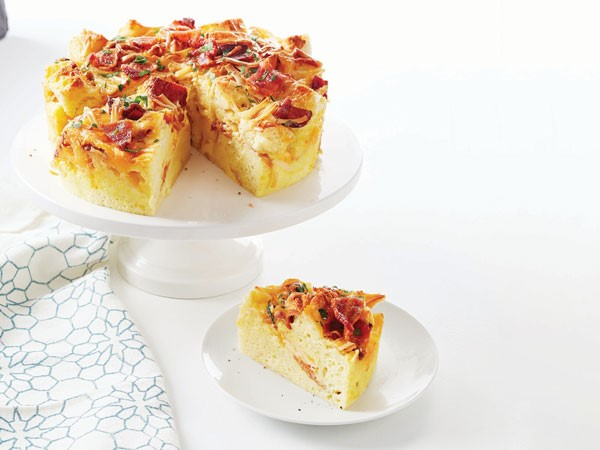 Round strata filled with bread, eggs, bacon, and melted cheese on white cake stand