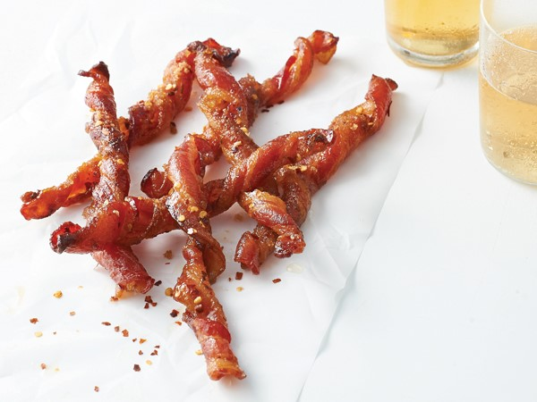 Bacon spirals on parchment paper sprinkled with red pepper flakes