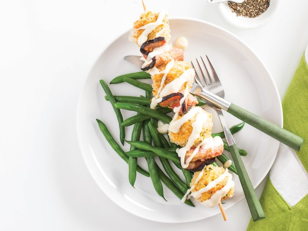 Breaded ham and cheese skewers over green beans