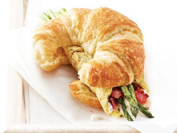 Asparagus omelet sandwiched between a sliced croissant