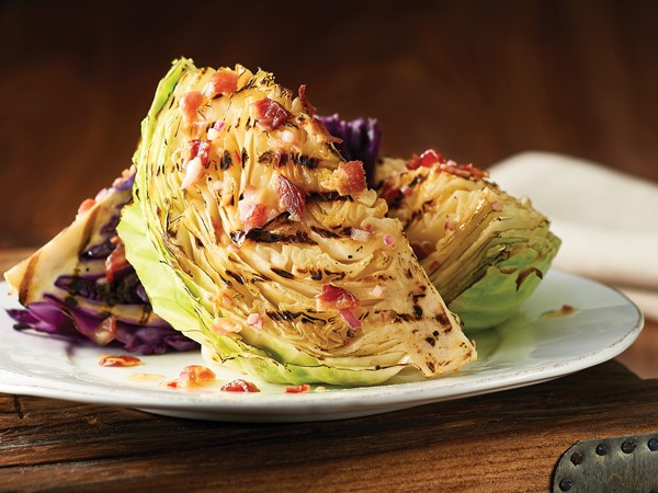 Plate of cabbage topped with bacon-mustard dressing