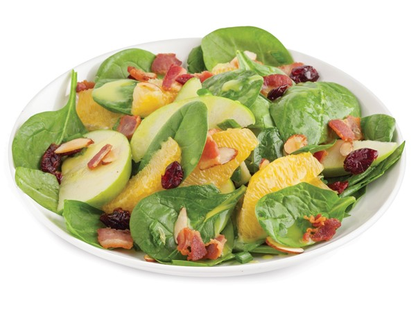 Plate of spinach topped with bacon, cranberries, green onions, apple slices, orange slices and sliced almonds