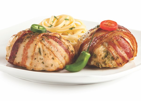 Plate of two bacon-wrapped chicken grillers, one garnished with a jalapeno, the other with a grape tomato
