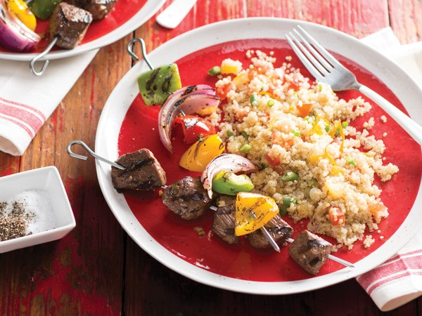 Quinoa salad next to grilled steak and vegetable kabobs